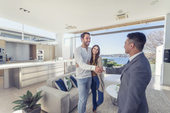 Real estate agent with couple in luxury home. They are shaking hands. There is a water view, kitchen and living room in the background. Couple are casually dressed. They are laughing. Agent is dressed in a suit and smiling. Wide angle.